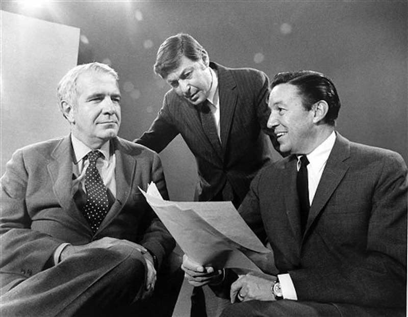 """This 1968 photo released by CBS shows """"60 Minutes"""" correspondents Harry Reasoner, left, and Mike Wallace, right, with creator and producer Don Hewitt on the set in New York. Wallace, famed for his tough interviews on """"60 Minutes,"""" has died, on Saturday, April 7, 2012. He was 93. (AP Photo/CBS Photo Archive)"""