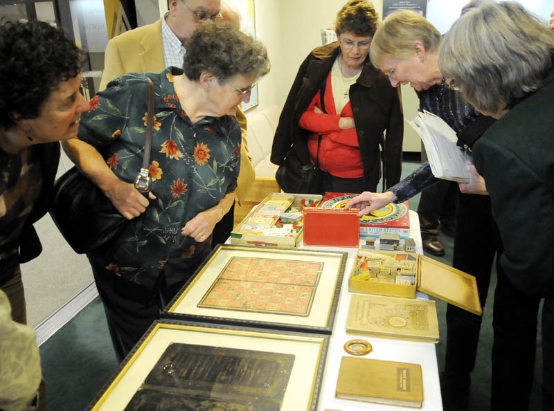 People examine books and games by Vienna native Milton Bradley following a Wednesday lecture by historian David Richards on the inventor's life at the Maine State Museum in Augusta.