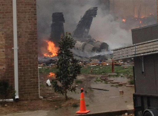 The fuselage of an F/A-18 Hornet burns after crashing into a residential building in Virginia Beach, Va., today.