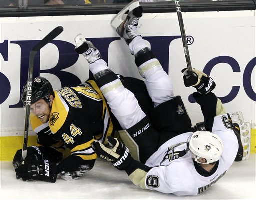 Boston Bruins defenseman Dennis Seidenberg (44) of Germany and Pittsburgh Penguins right wing Pascal Dupuis (9) crash along the boards during the third period of an NHL hockey game in Boston, Tuesday, April 3, 2012. The Penguins won 5-3.