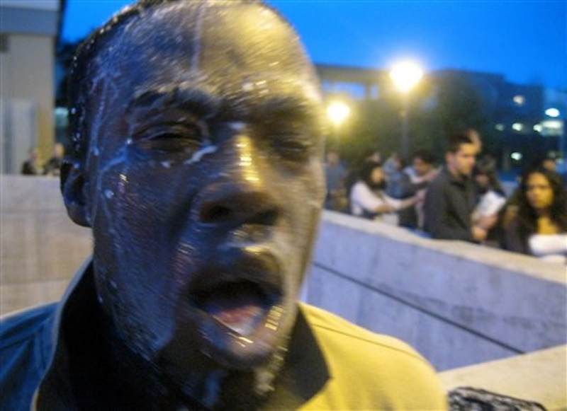 Nnaemeka Alozie, campaign manager for David Steinman, reacts with milk on his face after being sprayed with pepper spray during a protest on Tuesday, April 3, 2012, in Santa Monica, Calif. Campus police pepper-sprayed as many as 30 demonstrators after Santa Monica College students angry over a plan to offer high-priced courses tried to push their way into a trustees meeting Tuesday evening, authorities said. (AP Photo/Courtesy David Steinman)