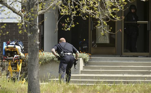 An Oakland police officer approaches the entrance to Oikos University in Oakland, Calif., today. A suspect is in custody in a shooting attack that has left at least seven people dead.
