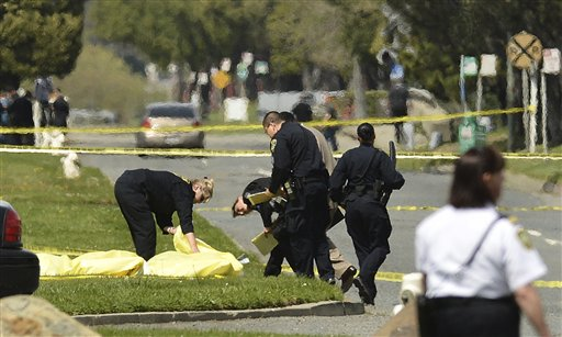 Police cover the bodies of some of the shooting victims near Oikos University in Oakland, Calif., today.