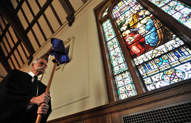 Staff Photo by Michael G. Seamans Richard Spear and others with the Holy Trinity Anglican Church mark Good Friday and the crucifixation of Jesus Christ during a service in Waterville. The Friday service precedes Easter, which celebrates Christ�s resurrection on the third day after his death. The Anglican church group rents space at Sacred Heart Church for their services.