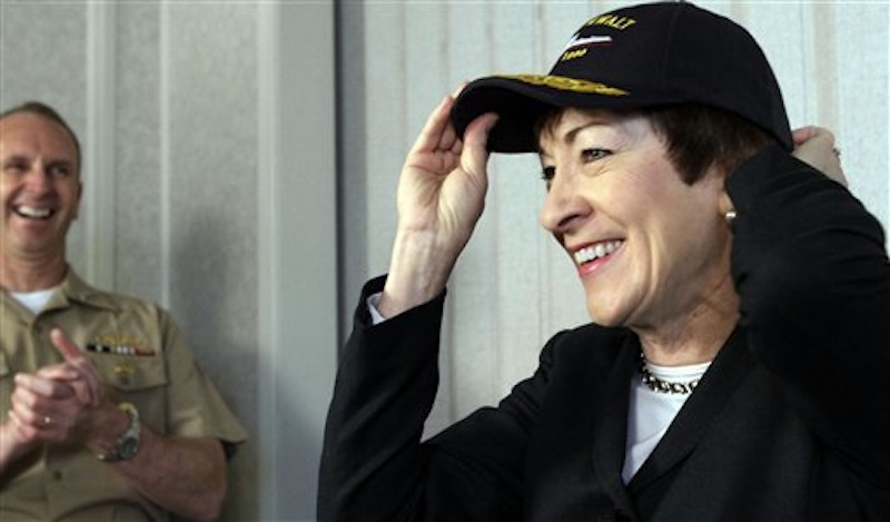U. S. Sen. Susan Collins, R-Maine, smiles as she places a cap on her head while Chief of Naval Operations Admiral Jonathan Greenert laughs during a news conference at Bath Iron Works, in Bath, Maine, on Wednesday, April 4, 2012. (AP Photo/Pat Wellenbach)