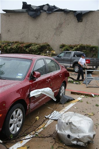 A car is damaged after a storm passed through in Arlington, Texas, today.