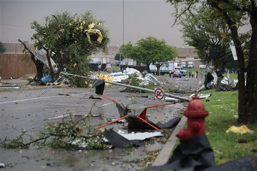 A pole and branches are scattered on the ground after a storm passed through Arlington, Texas, today.