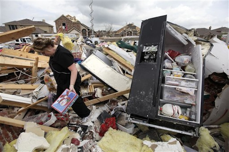 Ashley Quinton walks through the tornado damaged home of her friend Sherry Enochs in hopes of finding personal items that can be salvaged Wednesday, April 4, 2012, in Forney, Texas. Enochs was babysitting three children, all under the age of 3, that survived the storm with only minor bumps and scrapes. (AP Photo/Tony Gutierrez) AP