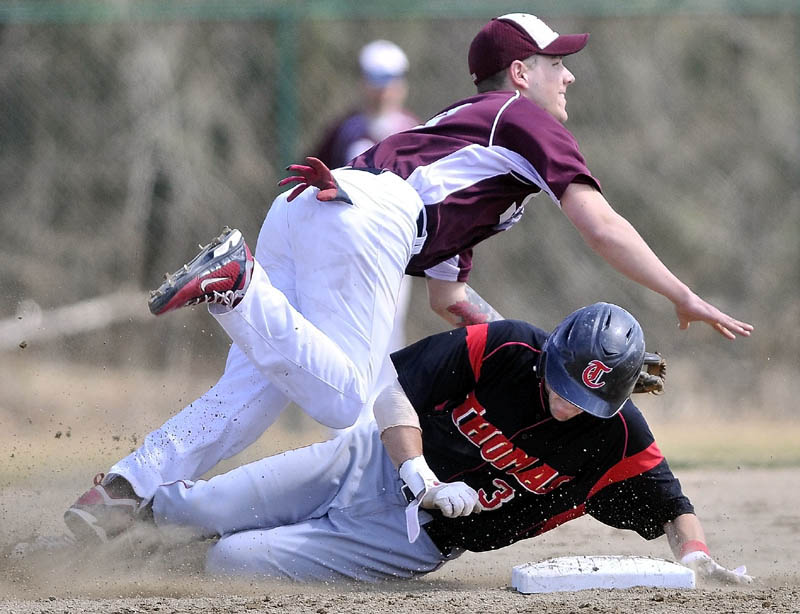 BREAK IT UP: Thomas' Jeff Richardson slides into second base as he tries to break up the double play attempt by University of Maine at Farmington second baseman Ian McAlister in the first game of a doubleheader Wednesday in Waterville.)