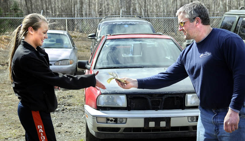 MONEY TRAIL: Rob Drummond, of Ready Road Service, hands 16-year-old Britany Whitaker $500 in cash Thursday from the sale of a car, center, that was impounded at his Augusta garage. The Jetta was seized from burglars who broke into Whitaker's house in February.