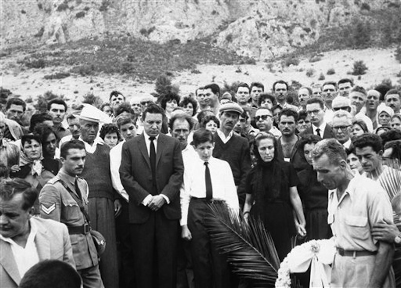 """In this Sept. 13, 1962 file photo, Mike Wallace stands before his son Peter's grave as the casket is lowered at Kamari Village, Peloponnesus, Greece, after Peter Wallace fell to his death in a accident while climbing a steep mountain in Greece. Behind Wallace is his stepson Andrew, and next to him is his son, Chris, 14, with his mother, Norma Leonard, now Mrs. Bill Leonard, and Mrs. Lorraine Wallace. Wallace, the dogged, merciless reporter and interviewer who took on politicians, celebrities and other public figures in a 60-year career highlighted by the on-air confrontations that helped make """"60 Minutes"""" the most successful primetime television news program ever, has died. He was 93. (AP Photo)"""