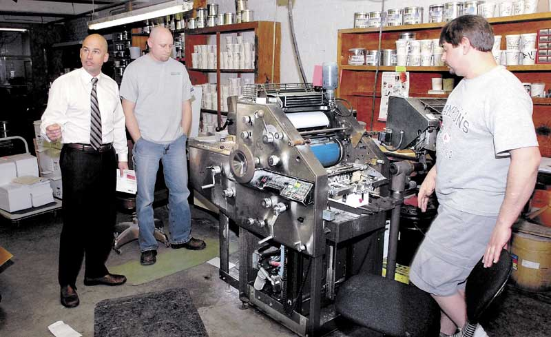 CLOSING: Jim Mitchell, left, co- owner of Atkins Printing Service in Waterville, speaks about the company as employees Randy Lovely, center, and Howard Dyer operate a press. The company is closing this month after 102 years in business.