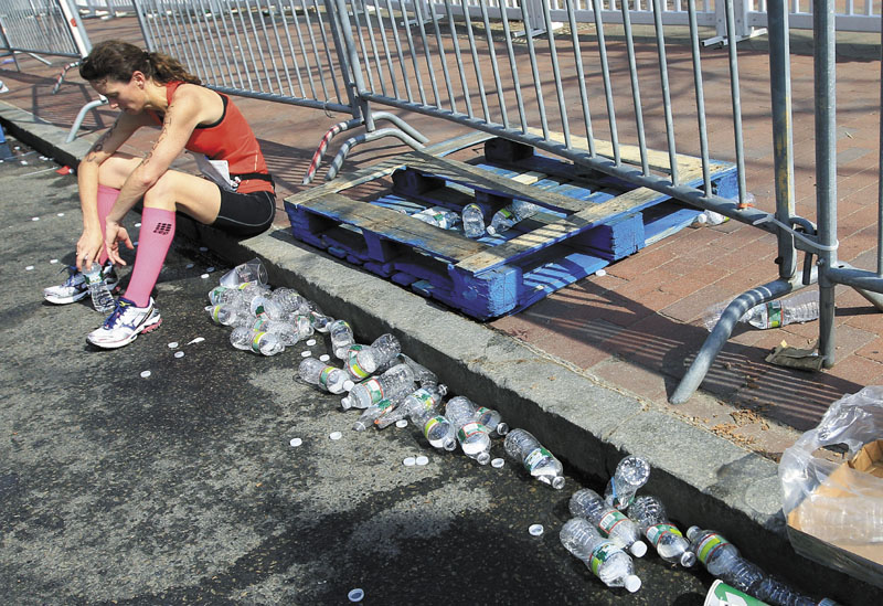 THAT'S ENOUGH: A tired runner rests near the finish area of the Boston Marathon on Monday in Boston. With temperatures in the 80s, this was the second-slowest Boston Marathon since 1985.