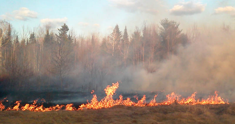 DRY CONDITIONS: The Maine Forest Service is warning about high fire danger after several wildfires statewide were reported Monday, including this one in Clinton. It burned about six acres of grass and brush before it was contained by the agency and Clinton Fire Department Monday evening, according to Lt. Jeffrey Currier of the forest service.