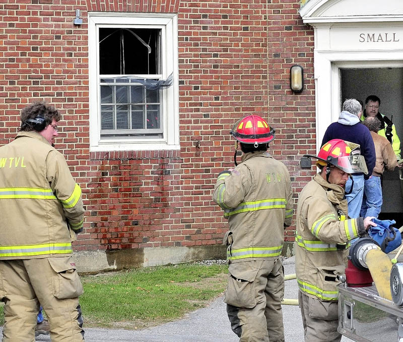 FIRE: Waterville firefighters gather outside the East Quad dormitory at Colby College near a dorm room window that was broken after fire from an unattended lit candle caused damage to the room on Thursday.