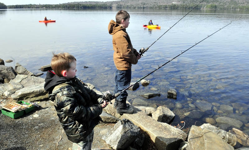 OPEN SEASON: Fishermen including Adden Ricci, left, and his brother Shane of Hartland and kayakers fished on Long Lake in Belgrade on Sunday.