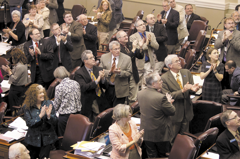 Legislators on the Republican side of the aisle stand and applaud visitors last week in the House Chamber. From cutbacks in MaineCare to slashed income taxes, Gov. Paul LePage and Maine's Republican-majority Legislature have left their mark.