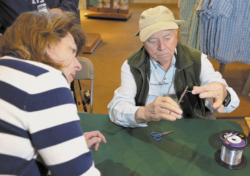 LIKE THIS: Lefty Kreh is quick to teach fishing intricacies, including showing Norma Nardone of Kennebunk how to tie a 6-loop clinch knot with forceps during a visit to L.L. Bean.