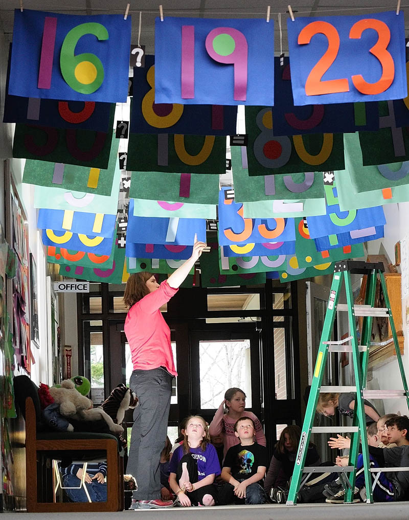 District Math Coach Sarah Caban points at an equation hanging from the ceiling during a lecture on Wednesday morning at Mount Vernon Elementary School. She and art teacher Dona Seegers co-taught a math and art class for third-graders under the Math Gate banners in the school's main hallway.