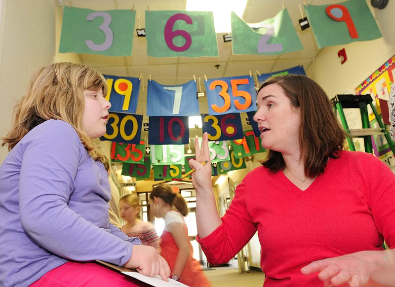 Third-grader Guinevere Kane works with District Math Coach Sarah Caban on an equation on Wednesday morning at Mount Vernon Elementary School. Caban and art teacher Dona Seegers co-taught a math and art class for third-graders under the Math Gate banners in the school's main hallway.