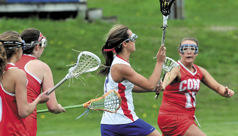 ON THE MOVE: Messalonskee's Kristyna Bernatchez weaves through Cony players, including Kevie Rodrique, right, during the Rams' 11-10 win Thursday in Oakland.