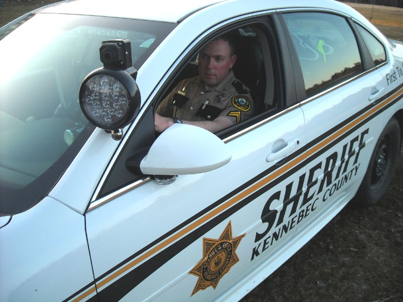 Corporal Scott Mills of the Kennebec County Sheriff's Office is seen in his cruiser with the thermal imaging camera mounted near the window.