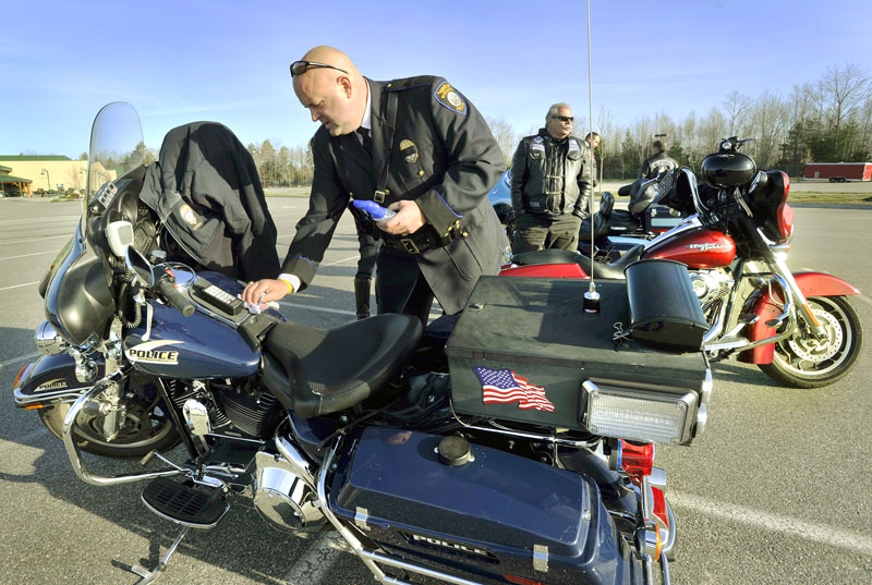 Detective Ray Williams of the Windham Police Department polishes his motorcycle before participating in the procession of law enforcement officers traveling to Greenland, New Hampshire to honor slain Police Chief Michael Maloney.