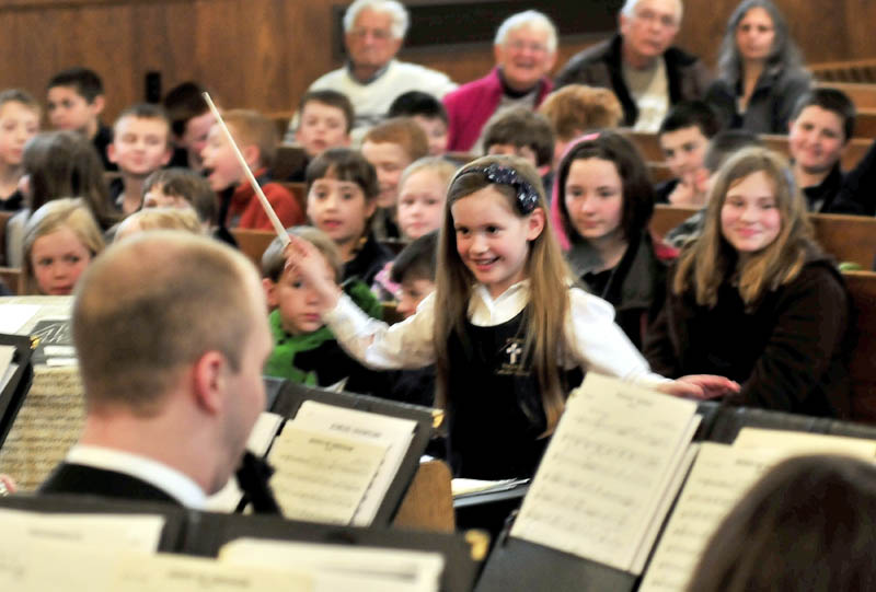 """MAESTRO DEBUT: St. John's Regional Catholic School kindergarten student Camden Cotnoir was selected to be guest conductor of the University of Maine in Orono Symphonic Band that performed to students and parents at Sacred Heart Church in Waterville on Monday. Cotnoir's brief performnce drew a standing ovation and conductor Chris White gave her the baton she used. A smiling Cotnoir said she was nervous and added,"""" I've never done this before."""""""