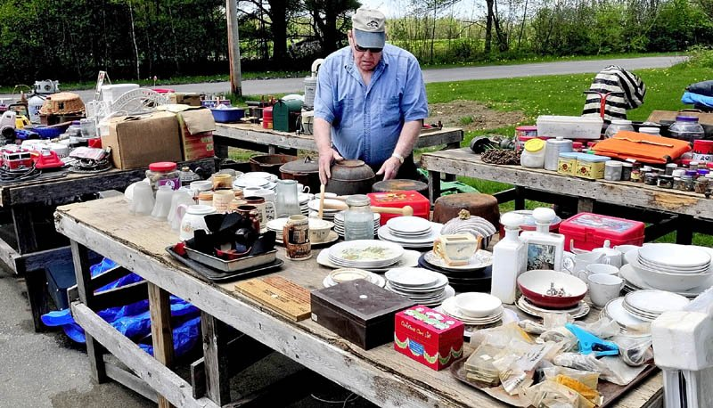 MAKE AN OFFER: Philip Goodell sets up merchandise on tables for the annual 10-mile yard sale at his home on the West Ridge Road in Cornville for this weekend's annual event.