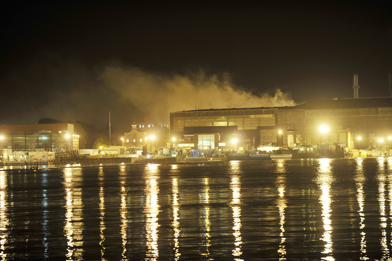 Smoke continues to rise from the fire aboard the USS Miami submarine, docked at the Portsmouth Naval Shipyard in Kittery, seen here from across the Piscataqua River in Portsmouth, N.H.