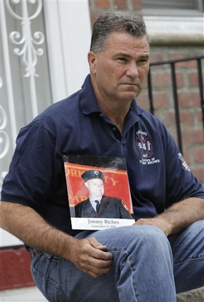 Retired firefighter Jim Riches poses for a picture with a photography of his son near his home in New York, Thursday, May 3, 2012. Riches, whose son was killed during the 2001 terrorist attacks on the World Trade center, will be among those to watch the arraignment of Khalid Sheikh Mohammed. The arraignment of the self-proclaimed mastermind of the Sept. 11 terror attacks and four other Guantanamo Bay prisoners will be broadcast to only six sites at four military bases in the U.S. Northeast, a Pentagon spokesman said Monday. (AP Photo/Seth Wenig)