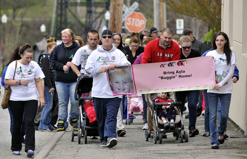 TRYING TO HELP: Participants of the Eyes Open Walk for Baby Ayla travel down Temple Street in downtown Waterville to help keep missing toddler Ayla Reynolds in the news on Saturday.