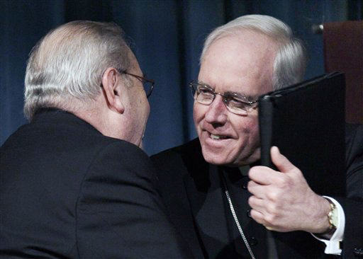 Bishop Richard Malone, right, hugs Bishop Edward Kmiec, left, during a news conference in Buffalo, N.Y., today following announcement by Pope Benedict XVI that Malone has been appointed bishop of the upstate New York diocese.