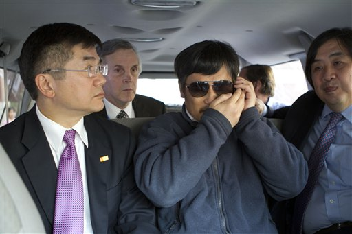 In this photo released by the US Embassy Beijing Press Office, blind lawyer Chen Guangcheng, center, accompanied by U.S. ambassador to China, Gary Locke, left, talks on a cellphone in a car en route from the U.S. Embassy to a hospital in Beijing, Wednesday. At second left is language attache James Brown and at right is U.S. State Department legal adviser Harold Koh.