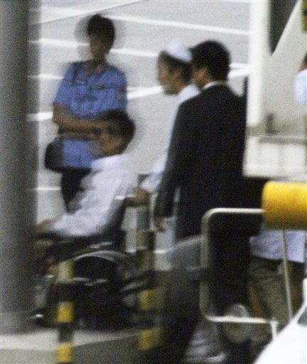 Chinese activist Chen Guangcheng, in a wheelchair, is helped to head to a commercial flight Saturday, May 19, 2012 at Beijing International Airport in Beijing. Chen was hurriedly taken from a hospital Saturday and boarded a plane that took off for the United States, closing a nearly monthlong diplomatic tussle that had tested U.S.-China relations. (AP Photo/Kyodo News) JAPAN OUT, MANDATORY CREDIT, NO LICENSING IN CHINA, HONG KONG, JAPAN, SOUTH KOREA AND FRANCE