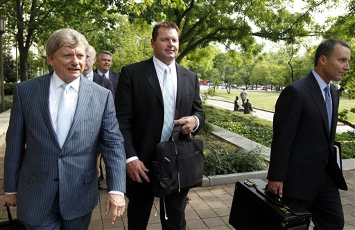 Former Major League Baseball pitcher Roger Clemens, center, leaves federal court on Tuesday in Washington.