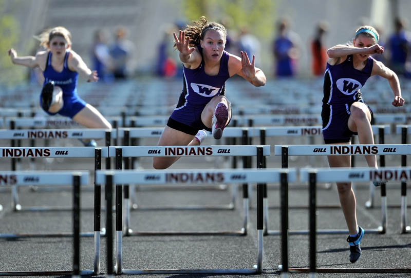 THE RACE IS ON: Waterville hurdlers Alex Jenson, center, and Olivia Thurston, right, and Lawrence High School's Katie Dudley compete in the 100-meter hurdles at the Community Cup track and field meet Friday at Skowhegan Area High School. Jenson won the race with a time 15:08.