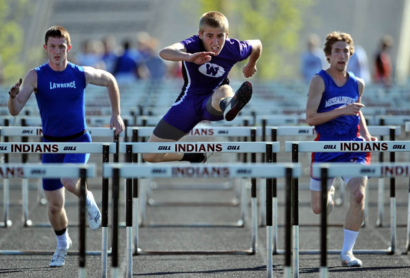 Waterville Senior High School's cpmepetes in the 110 meter hurdles at the Community Cup track and field meet at Skowhegan Area High School on Friday. Lawrence High School's Zachary Ricker is left and Messalonskee High School's Zach Sutherland is on the right.
