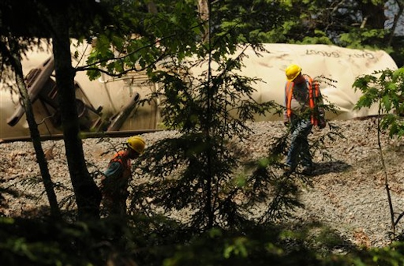 Pan-Am Railroad personnel work to repair the damaged rails on Saturday, May 26, 2012 near the Orrington-Bucksport town line after four tanker cars derailed on Friday sending two of the tankers into the Penobscot River. (AP Photo/Bangor Daily News, Kevin Bennett)