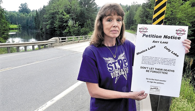 Sandra Mitchell, seen holding a petition at the Higgins Stream bridge in Harmony in July 2011, is stepping up her fight against domestic violence with a fundraising drive to add memorial gardens at several bridges that she worked to have renamed to honor past victims of violence.