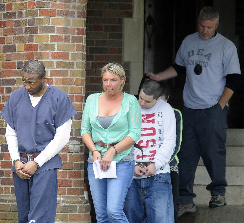ARRESTS: Maurice McCray, right, leads a line of people arrested Tuesday morning — including Tara Pelletier and Justin LaCroix, at left, by federal and state authorities at the Maine Criminal Justice Academy in Vassalboro. Officers from several agencies said they made 10 arrests across central Maine stemming from a months-long drug investigation. Suspects were processed by federal agents at the Maine Criminal Justice Academy before being sent to jail.
