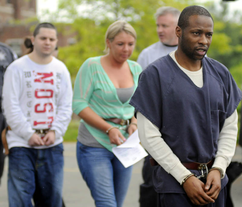 ARRESTS: Maurice McCray, right, leads a line of people arrested Tuesday morning — including Justin LaCroix and Tara Pelletier, at left, by federal and state authorities at the Maine Criminal Justice Academy in Vassalboro. A federal DEA agent is seen in the far back. Officers from several agencies said they made 10 arrests across central Maine stemming from a months-long drug investigation. Suspects were processed by federal agents at the Maine Criminal Justice Academy before being sent to jail.