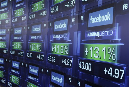Electronic screens show the price of Facebook shares after they began trading today in New York.