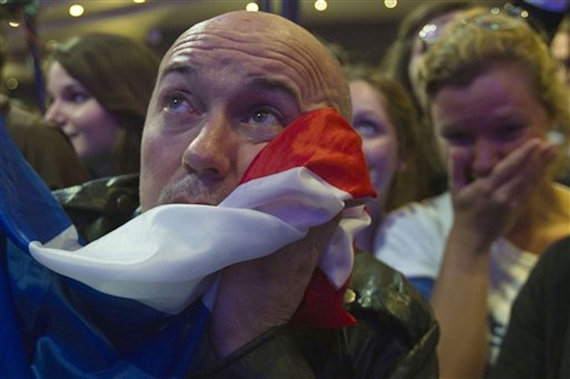 A supporter of outgoing French President Nicolas Sarkozy's Union for a Popular Movement (UMP) covers his face with the national flag as the preliminary results of the second round of the presidential elections were announced at UMP headquarters in Paris Sunday May 6, 2012. The first results showed a 52 percent lead for Socialist Party candidate Francois Hollande. (AP Photo/Michel Euler)
