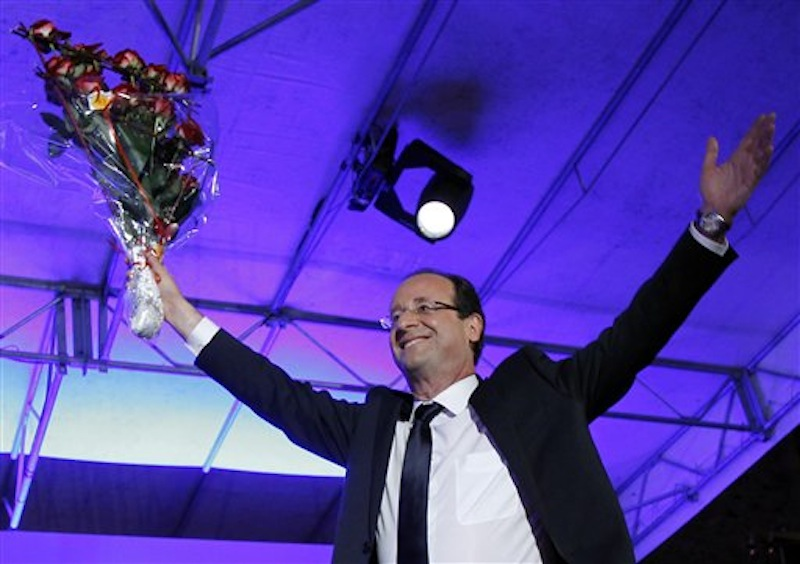 President-elect Francois Hollande holds a bouquet of roses after delivering his speech in Tulle, central France, Sunday, May 6, 2012. Francois Hollande defeated Sarkozy on Sunday to become France's next president, Sarkozy conceded defeat minutes after the polls closed. (AP Photo/Christophe Ena)