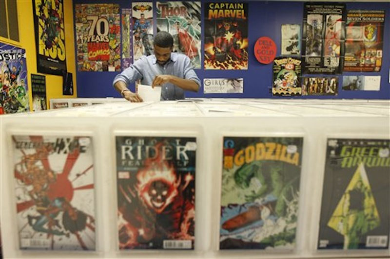 Ron Ackins, 29, of Philadelphia, checks out back issues of comics at Fat Jack's Comicrypt, Friday, May 4, 2012, in Philadelphia. Like hundreds of other comic specialty shops in 46 countries, the store is participating in Free Comic Book day on Saturday, May 5, which sees shops give away free copies of new and reprinted comics from some 40 publishers, including Marvel, DC, Archie, Image, Dark Horse, Valiant and Dynamite, among others, to promote the growth of the medium and garner new readers, some of whom may have been exposed to heroes through television and films. Free Comic Book day started 11 years and continues to expand, said Joe Field, who helped organize the inaugural event. This year, some 3.5 million free comics will be handed out. (AP Photo/Matt Rourke)
