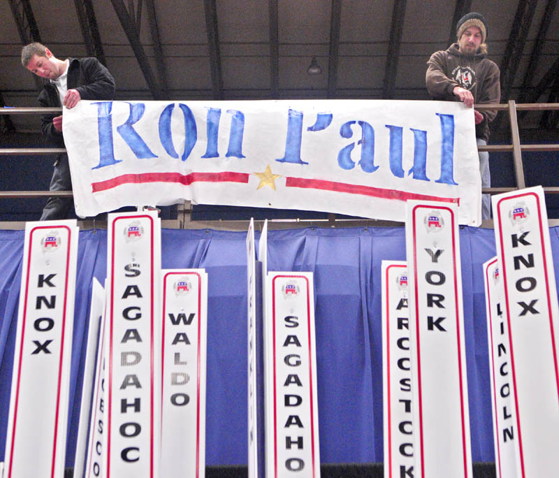 Toby Hoxie, of Hallowell, left, and Chad Libby, of Winthrop, hang up a sign for presidential candidate Ron Paul on Friday afternoon at the Augusta Civic Center. The state Republican convention opens this morning and runs through Sunday.