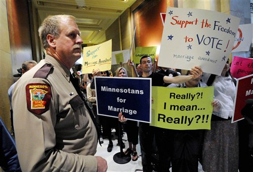 In this May 19, 2011 file photo, a state trooper stands by as demonstrators on both sides of the gay marriage issue gather outside the Minnesota House in St. Paul, Minn. Poll after poll shows public support for same-sex marriage steadily increasing, to the point where it's now a majority viewpoint. Yet in all 32 states where gay marriage has been on the ballot, voters have rejected it. It's possible the streak could end in November 2012, when Maine, Maryland, Minnesota and Washington state are likely to have closely contested gay marriage measures on their ballots. For now, however, there remains a gap between the national polling results and the way states have voted. (AP Photo/Jim Mone, File)