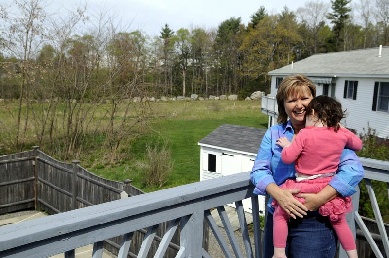 Jean Goding holds her granddaughter, Julia Luszczki, 2, on the deck of Goding's Augusta home Sunday. The proposed site for a new Augusta Spiritualist Church is behind her house, and oding and several other neighbors object to the planned location.