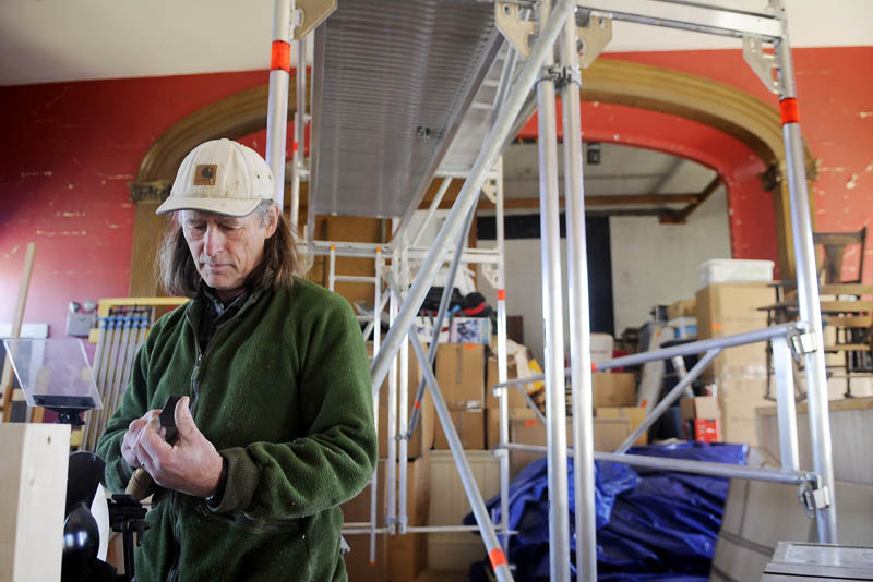 Erik Groenhout insects a woodworking tool he sharpened Monday in the interior of the former Odd Fellows Lodge he is restoring in Mount Vernon. The Dutch woodworker is restoring the prominent structure on Minnehonk Lake to open a cabinet making business.